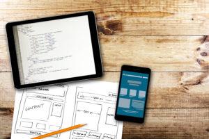 Website development, Wireframe Sketch And Programming Code On Digital Tablet